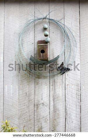Old vintage birdhouse and garden decor with wire and metal butterfly hanging on a wall or fence with lots of copy space.  - stock photo