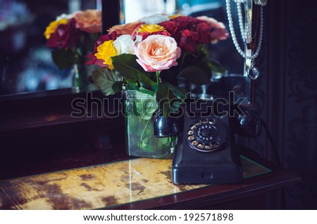 Old vintage black rotary phone and a bouquet of fresh roses on an old dresser in interior, retro style home decor - stock photo