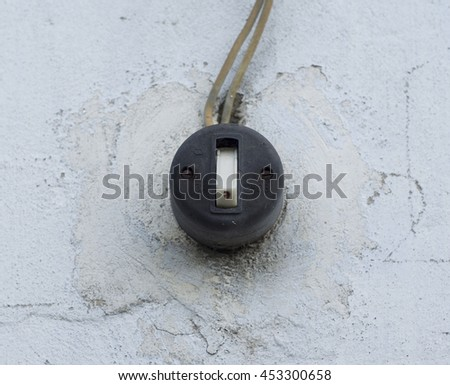 Old vintage black switch on a white wall outdoors