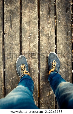 Old vintage blue shoes and legs in a blue jeans on the wooden floor  - stock photo