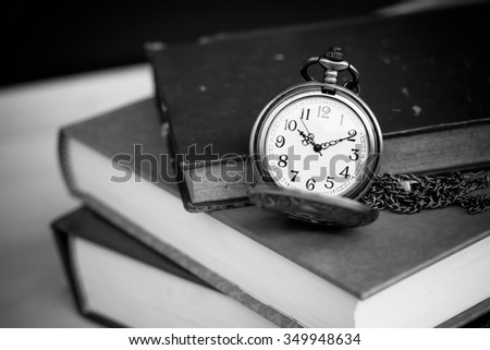 Old vintage books and pocket watches on wooden desk. Black and white style filtered photo - stock photo