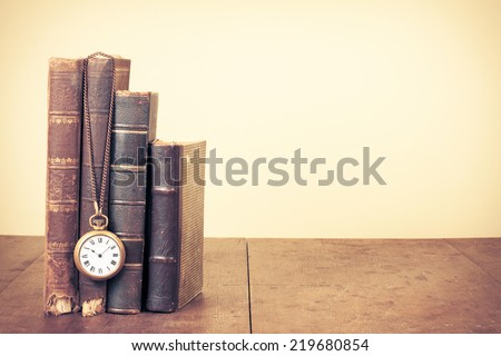 Old vintage books and pocket watches on wooden desk. Retro style filtered photo - stock photo