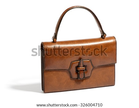 Old vintage brown ladies leather handbag with a handle and front clasp isolated on white in a fashion accessories and collectibles concept