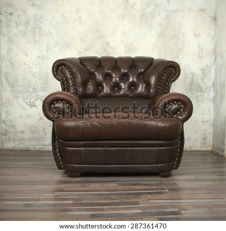 Old vintage brown leather chair in empty room - stock photo