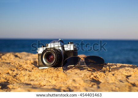 Old vintage camera and sunglasses over on a rock against the sea landscape