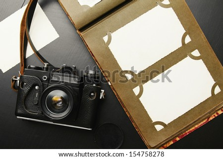 old vintage camera with album and blank pictures - stock photo