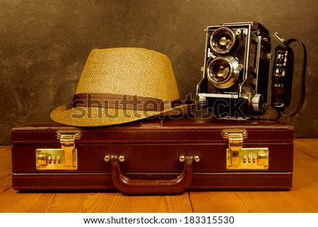 Old vintage camera  with fedora hat on rustic briefcase  - stock photo