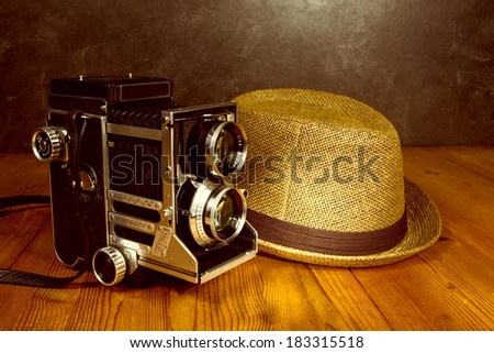 Old vintage camera with photographer fedora hat - stock photo