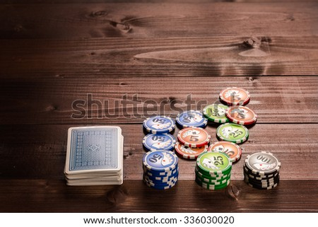 old vintage cards and a gambling chip on a wood table. - stock photo