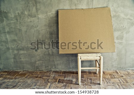 Old vintage chair and empty cardboard in grungy interior. Loneliness, estrangement, alienation concept. - stock photo