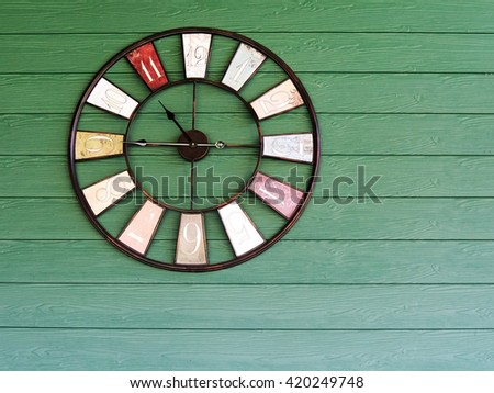 Old vintage clock on green wooden plank wall background. - stock photo
