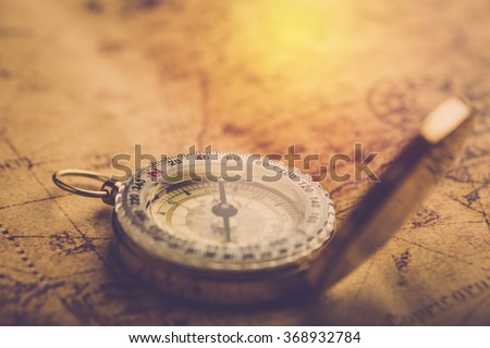 Old vintage compass on vintage map. Vintage filter. - stock photo