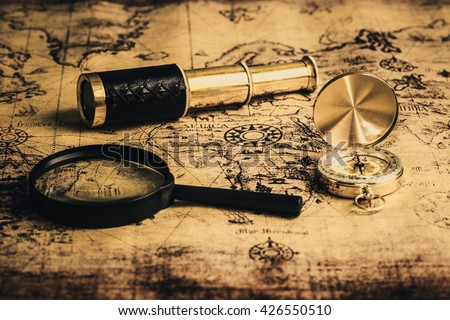Old vintage compass ,telescope and magnifying glass on vintage map - stock photo