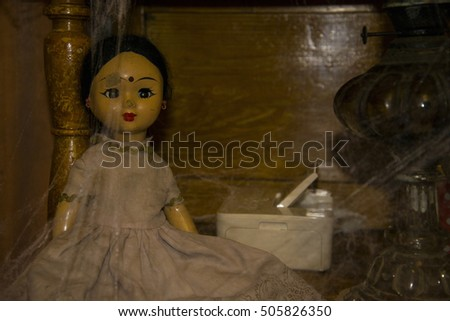 Old vintage doll stands on the old, dusty wardrobe which is covered with cobwebs.
