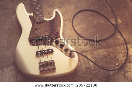 old vintage electric bass guitar on basement floor - stock photo
