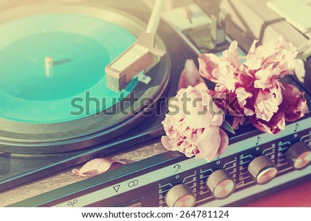 Old vintage good looking turntable playing a track with vinyl and flowers - stock photo