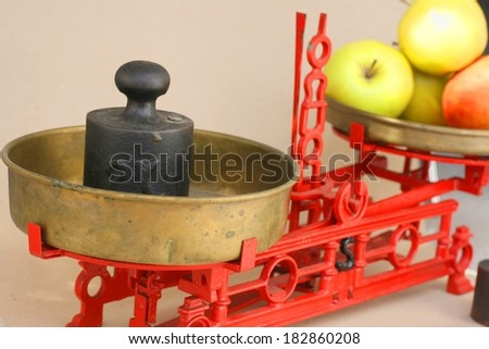 Old vintage kitchen balance scale with apples and weights - stock photo