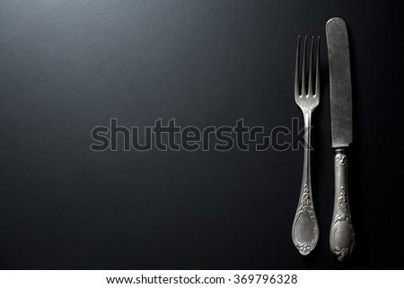 old vintage knife and fork on black background - stock photo