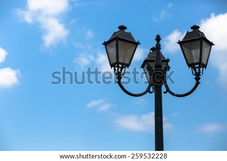 Old vintage lamppost on the blue sky background. Space for text. - stock photo