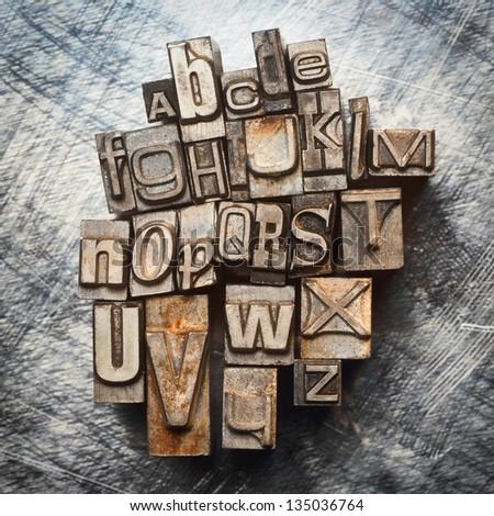 Old vintage letterpress type letters alphabet grunge background - stock photo