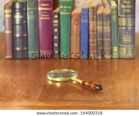 old vintage magnifying glass on wooden table with books row - stock photo