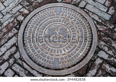 Old vintage manhole on the grey pavement - stock photo