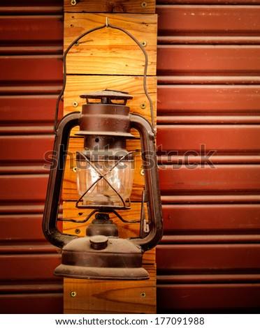 Old vintage metal oil lantern on metal wood wall - stock photo