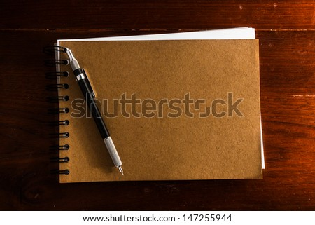 Old vintage note book with pen on wooden table - stock photo