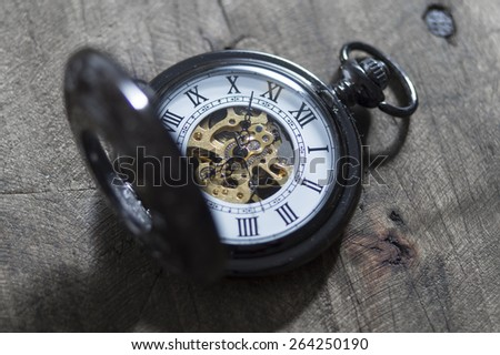 old vintage pocket watch lying on  wooden background - stock photo