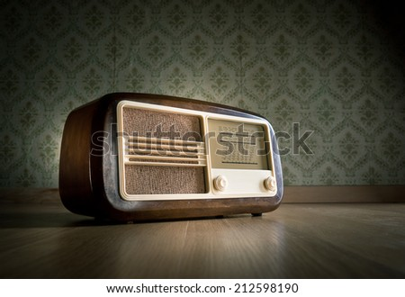 Old vintage radio on hardwood floor with retro wallpaper on background. - stock photo