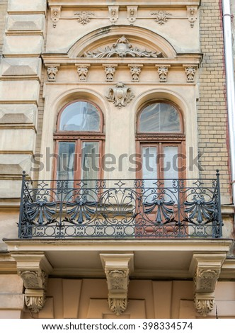 Old vintage retro balcony with columns and ornaments on an old building with windows on one of the streets of Lviv, Ukraine