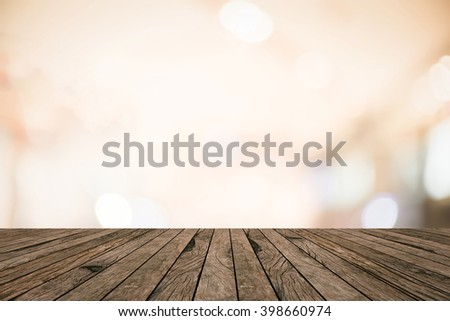 old vintage retro brown wood tabletop with blurred abstract store mall bokeh light warm tone background boarder:grunge aged wooden with blurry orange color backdrop.show advertise product on display - stock photo
