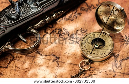 Old vintage retro compass and antique pistol on ancient world map. Vintage still life. Travel geography navigation concept background.