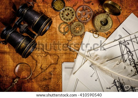 Old vintage retro compass and binoculars on ancient world map. Vintage still life. Travel geography navigation concept background. - stock photo