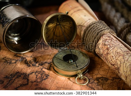 Old vintage retro compass and spyglass on ancient world map. Vintage still life. Travel geography navigation concept background. - stock photo