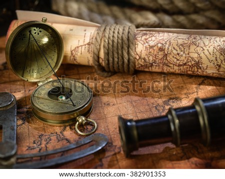 Old vintage retro compass, measuring devices and magnifying glass on ancient world map. Vintage still life. Travel geography navigation concept background.