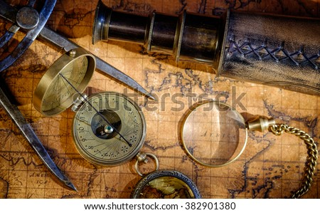 Old vintage retro compass, measuring devices, magnifying glass and spyglass on ancient world map. Vintage still life. Travel geography navigation concept background. - stock photo