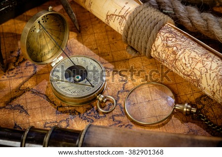 Old vintage retro compass, spyglass and magnifying glass on ancient world map. Vintage still life. Travel geography navigation concept background. - stock photo