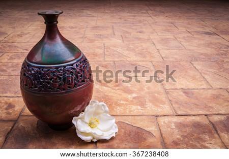 Old vintage retro hand made Islamic style vase with muslim ornaments on a brick background with white rose flower, beautiful arabian jar photo, ramadan kareem - stock photo