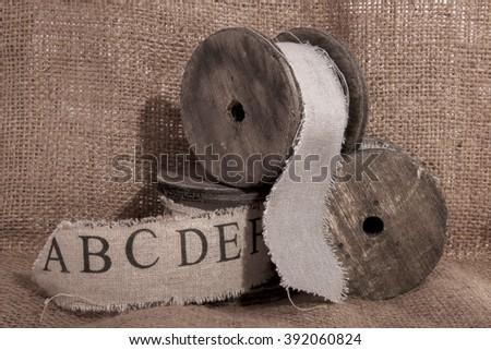 Old vintage ribbon spools on jute background - stock photo