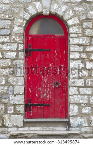 Old vintage rustic exterior red door detail on old brick building. - stock photo