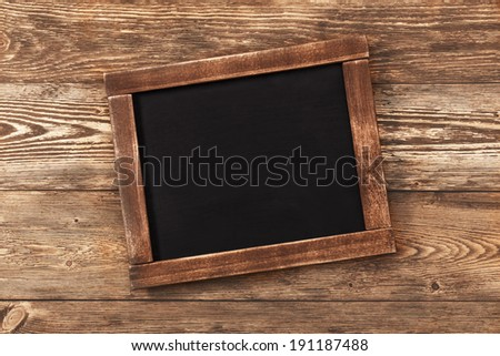 Old vintage school slate on wood background on grunge style - stock photo