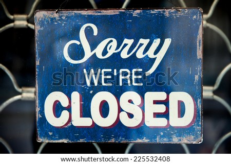 Old vintage sign saying Sorry We're Closed - stock photo