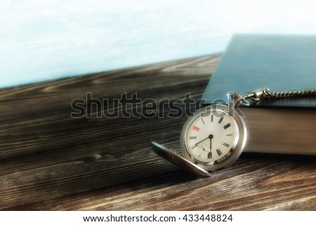 Old vintage silver pocket watch and book with black cover on wooden table. Blurred. Soft focus - stock photo