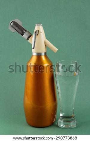 Old vintage siphon and glass of water on a green background - stock photo
