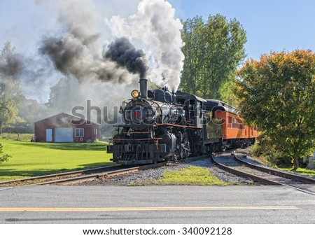 Old Vintage Steam Engine Arriving At The Train Depot - stock photo