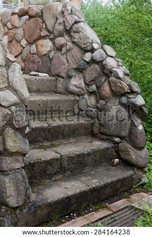 Old vintage stone stair way near house and green grass - stock photo