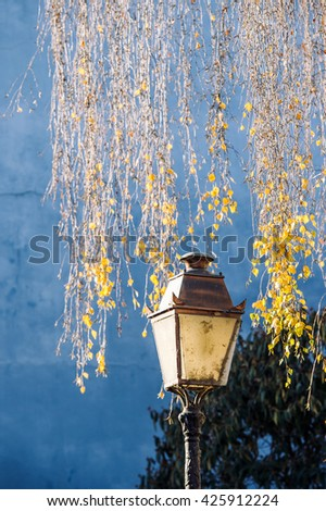 Old vintage street lamp lantern with yellow leaf tree in the background and beautiful blue wall - stock photo