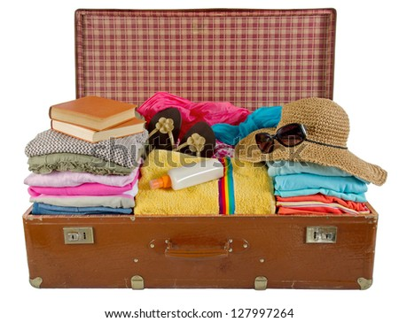 Old vintage suitcase packed with women's clothes, hat, books, sunglasses and beach towel - stock photo
