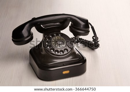 Old vintage telephone on wooden table - stock photo